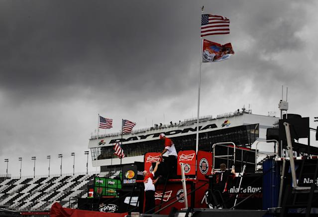 Crew members work on pit road under threatening skies during practice for Sunday's NASCAR Daytona 500 Sprint Cup series auto race in Daytona Beach, Fla., Friday, Feb. 21, 2014. (AP Photo/Terry Renna)