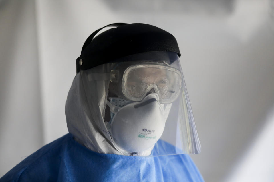 A healthcare worker, dressed in full protective gear, waits to test a person for the new coronavirus inside a mobile diagnostic tent, in the Coyoacan district of Mexico City, Friday, Nov. 13, 2020. Mexico City announced Friday it will order bars closed for two weeks after the number of people hospitalized for COVID-19 rose to levels not seen since August. (AP Photo/Eduardo Verdugo)