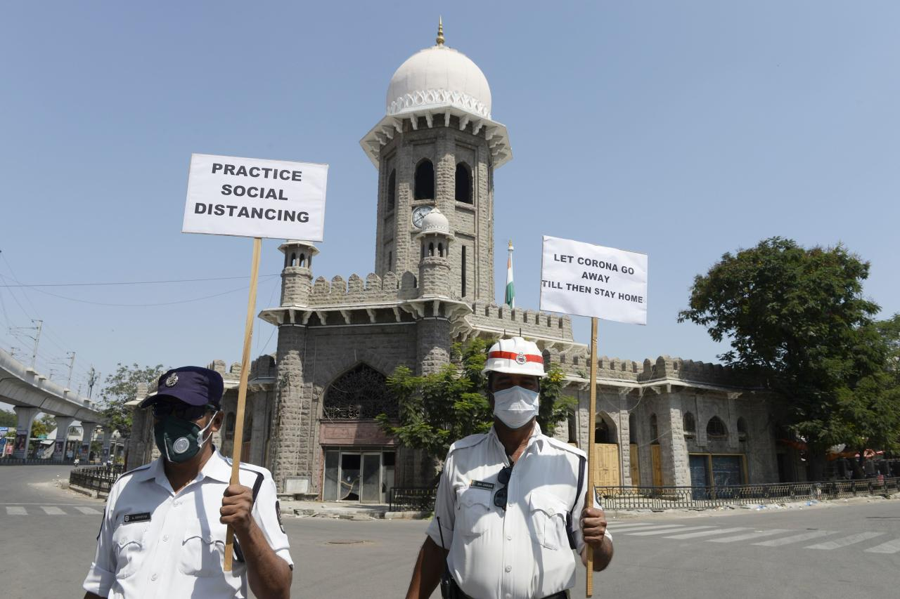 Traffic police personnel hold placards on a deserted road during a one-day nationwide Janata (civil) curfew imposed as a preventive measure against the COVID-19 coronavirus, in Hyderabad on March 22, 2020. - Nearly one billion people around the world were confined to their homes, as the coronavirus death toll crossed 13,000 and factories were shut in worst-hit Italy after another single-day fatalities record. (Photo by NOAH SEELAM / AFP) (Photo by NOAH SEELAM/AFP via Getty Images)