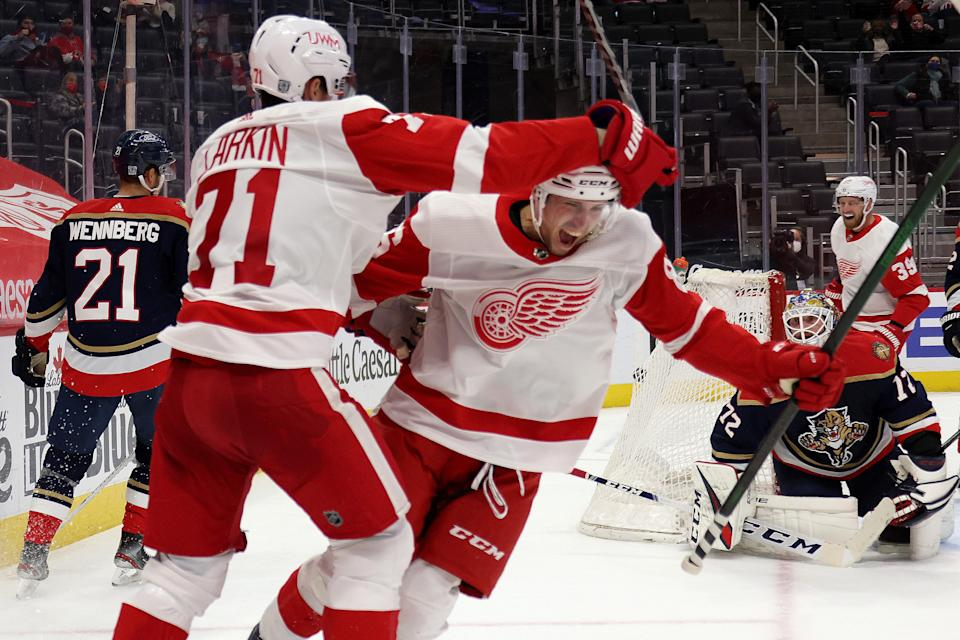 Red Wings forward Mathias Brome celebrates his first career goal with Dylan Larkin during the second period of the Wings' 2-1 win on Saturday, Feb. 20, 2021, at Little Caesars Arena.