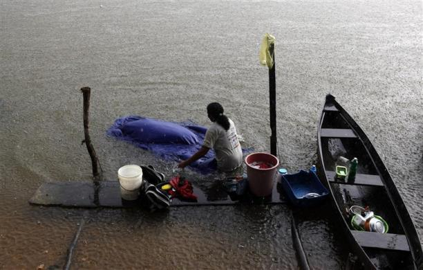 A woman washes clothes in the Tapajos river in the village of Pimental in Itaituba, state of Para May 26, 2012.