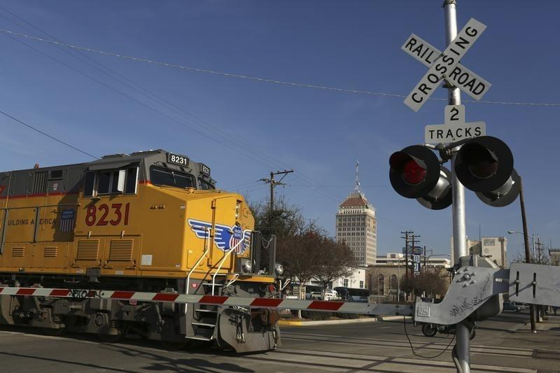 Freight locomotive rolls across an intersection in Fresno