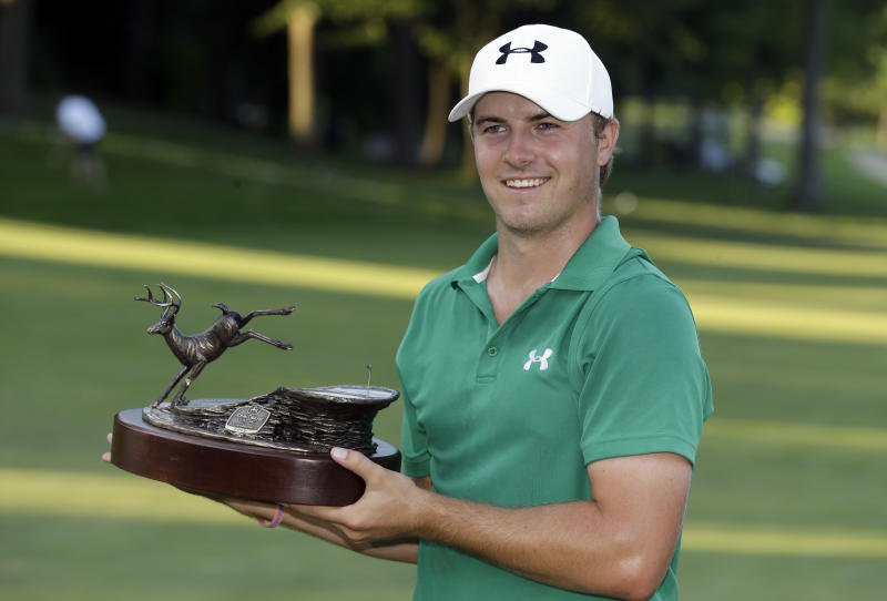 Jordan Spieth holds the trophy after winning the John Deere Classic golf tournament, Sunday, July 14, 2013, at TPC Deere Run in Silvis, Ill. Spieth defeated Zach Johnson and David Hearn on the fifth hole of a playoff. (AP Photo/Charlie Neibergall)
