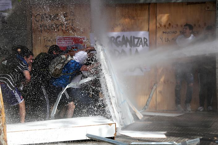 Demonstrators take cover as they are sprayed by security forces with a water cannon during a protest against Chile's state economic model in Santiago, Chile on Oct. 23, 2019. (Photo: Ivan Alvarado/Reuters)