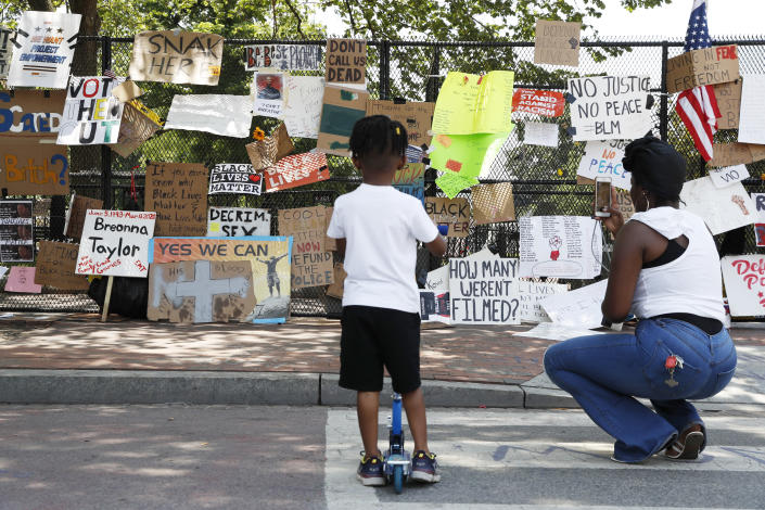 Diamond Lee of Washington, helps her son Jaylen, 4, look at signs hanging on a police fence at 16th and H Street, Tuesday, June 9, 2020, near the White House in Washington, after days of protests over the death of George Floyd, a black man who was in police custody in Minneapolis. Floyd died after being restrained by Minneapolis police officers. (AP Photo/Jacquelyn Martin)