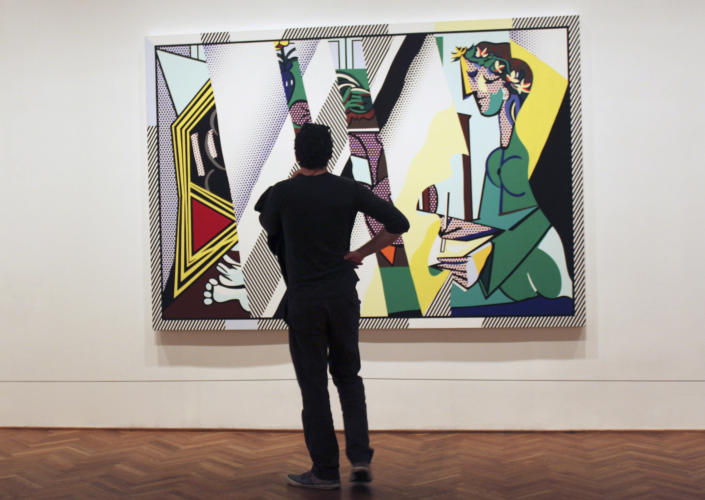 """In this May 11, 2012 photo, a visitor to the Art Institute of Chicago stands in front of """"Reflections on 'Interior with Girl Drawing'"""" by the late pop artist Roy Lichtenstein. The museum has opened """"Roy Lichtenstein: A Retrospective,"""" which runs through Sept. 3 before traveling to Washington, London and Paris. (AP Photo/Caryn Rousseau)"""