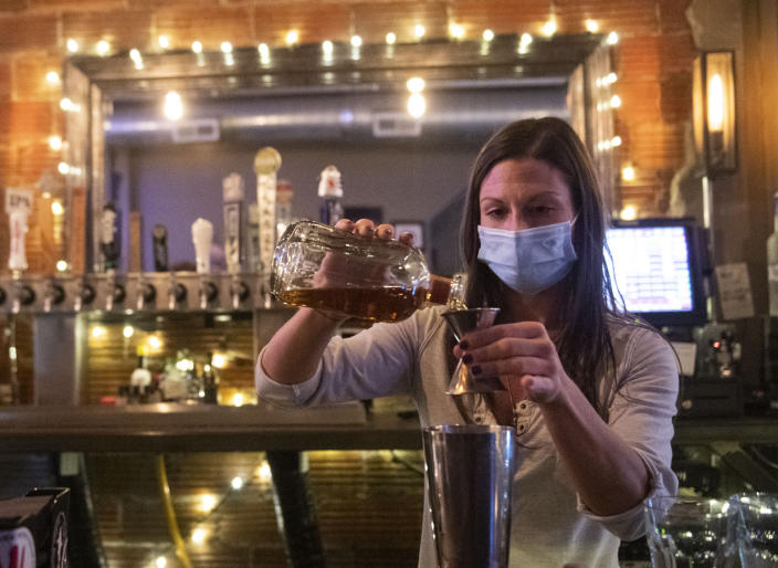 FILE - In this Nov. 23, 2020, file photo, Bartender Kellie Mottiqua prepares drinks at Bridgetown Taphouse in Ambridge, Penn. Not willing to wait for more federal help, states have been moving ahead with their own coronavirus relief packages. In Pennsylvania, Gov. Tom Wolf, a Democrat, in February 2021, signed legislation using $145 million in reserves from a worker's compensation fund for grants of up to $50,000 to owners of hard-hit bars, restaurants and hotels. The money is expected to be available next month. (Emily Matthews/Pittsburgh Post-Gazette via AP)