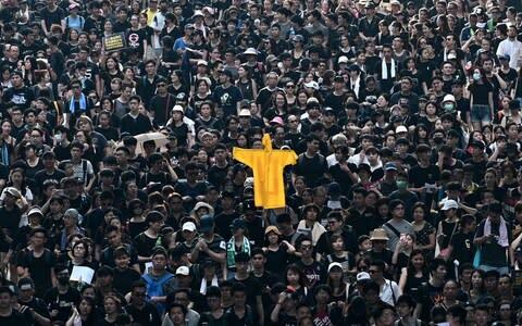 <span>Protesters hold up a yellow raincoat to pay tribute to a citizen who killed himself during the anti extradition bill demonstrations</span> <span>Credit: AFP </span>