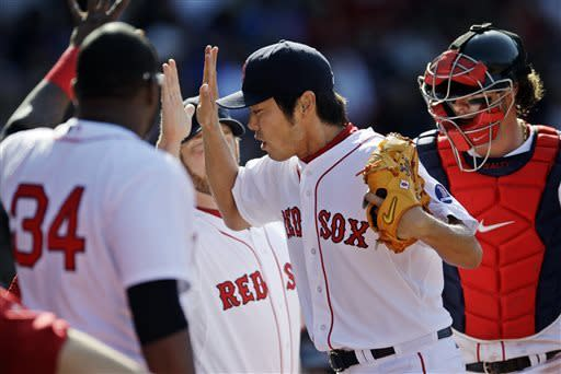 Boston Red Sox relief pitcher Koji Uehara, of Japan, is congratulated by teammates including David Ortiz after working the eighth inning in relief during a baseball game against the Houston Astros at Fenway Park in Boston, Sunday, April 28, 2013. (AP Photo/Mary Schwalm)
