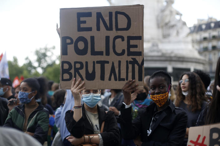 FILE - In this June 9, 2020 file photo, demonstrators hold a placard during a rally against racism in Paris after George Floyd's death in the U.S. As videos helped reveal many cases of police brutality, French civil rights activists voiced fears that a new security law would threaten efforts by people from minorities and poor neighborhoods to document incidents involving law enforcement officers. French President Emmanuel Macron's government is pushing a new security bill that would notably make it illegal to publish images of officers with intent to cause them harm. (AP Photo/Thibault Camus, File)