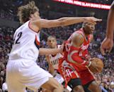 Houston Rockets' Dwight Howard (12) shoots against Portland Trail Blazers' Robin Lopez (42) and Nicolas Batum (88) during the first half of game six of an NBA basketball first-round playoff series game in Portland, Ore., Friday May 2, 2014. (AP Photo/Greg Wahl-Stephens)