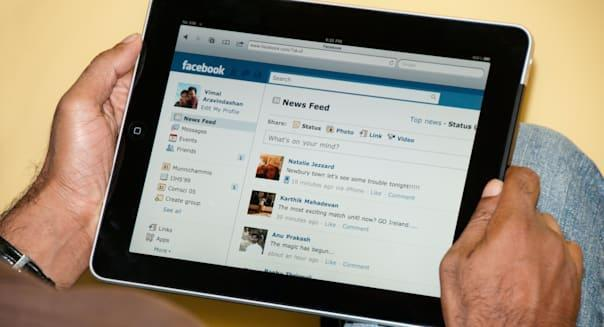 Close up view of a man using Facebook with iPad