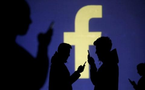 Silhouettes of mobile users are seen next to a screen projection of Facebook logo - Credit: Dado Ruvic/REUTERS