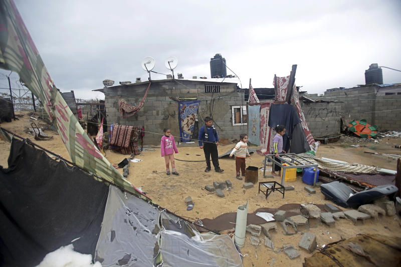 Palestinian children play at a damaged backyard of their family house following heavy rains in Gaza City, Saturday, Dec. 14, 2013. Rescue workers evacuated more than 5,000 Gaza Strip residents from homes flooded by four days of heavy rain, using fishing boats and heavy construction equipment to pluck some of those trapped from upper floors, an official said Saturday. (AP Photo/Adel Hana)