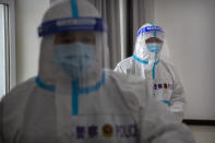 Security officers in protective suits stand in a hallway with rooms for video meetings with inmates at the visitors' hall at the Urumqi No. 3 Detention Center in Dabancheng in western China's Xinjiang Uyghur Autonomous Region on April 23, 2021. (AP Photo/Mark Schiefelbein)