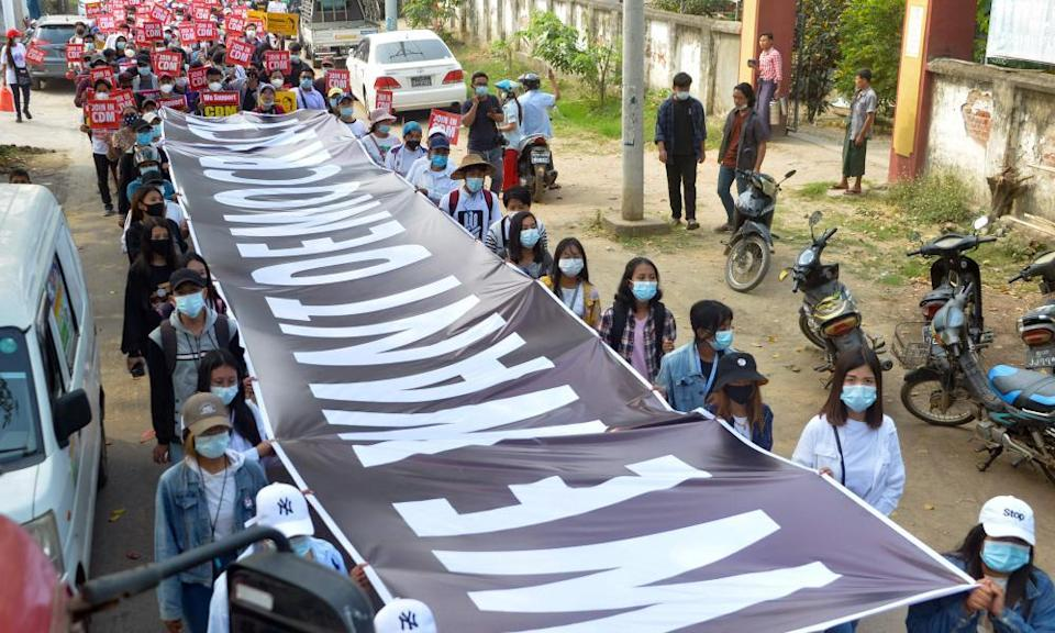 Protesters carry a banner that reads: 'We want democracy' during a demonstration against the military coup in Naypyidaw.