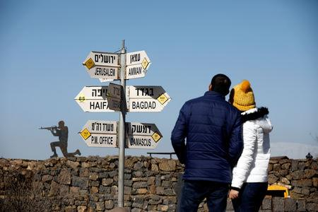 A couple look towards signs pointing out distances to different cities, on Mount Bental, an observation post in the Israeli-occupied Golan Heights that overlooks the Syrian side of the Quneitra crossing, Israel