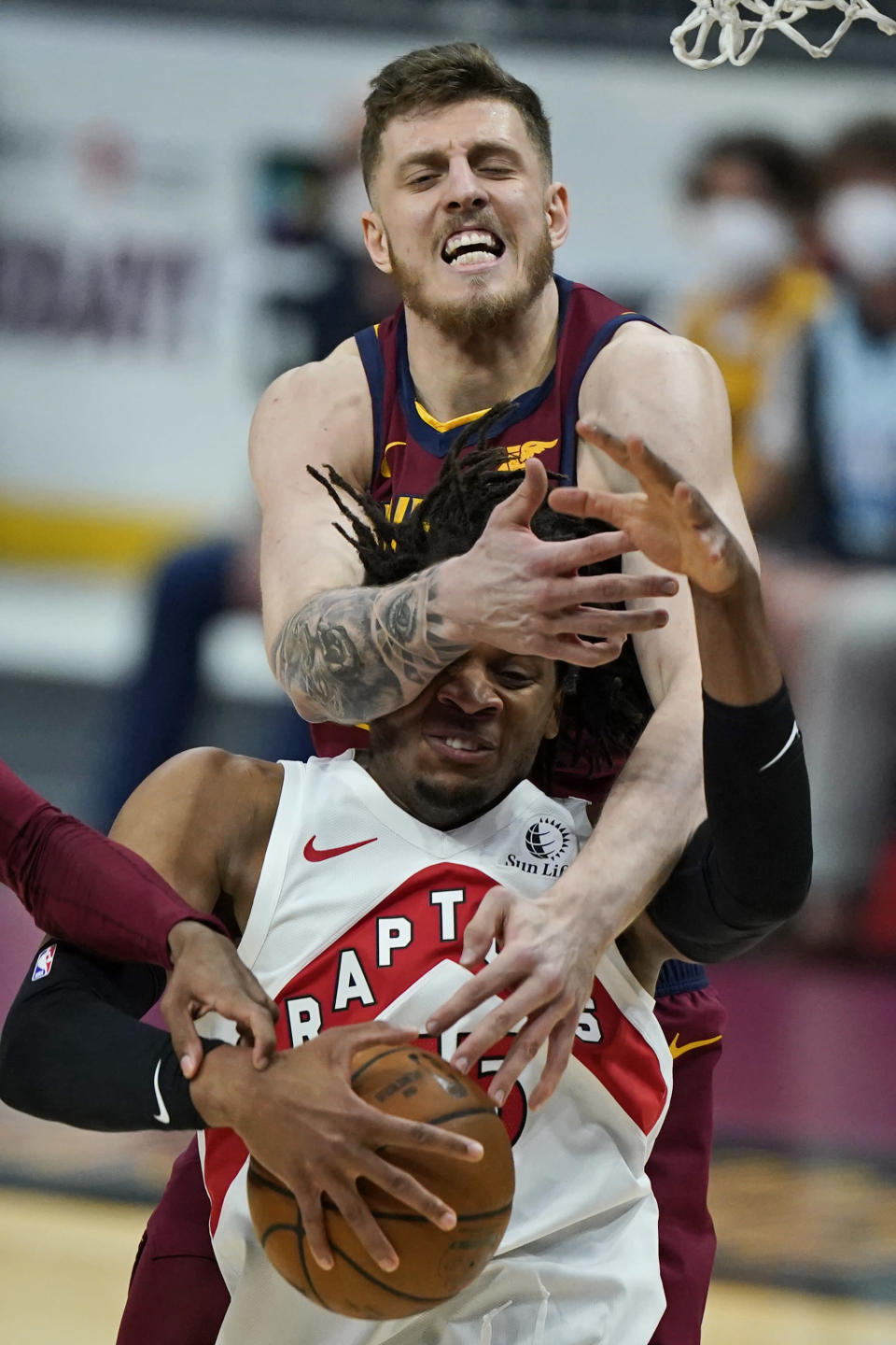 Cleveland Cavaliers Isaiah Hartenstein, top, knocks the ball loose from Toronto Raptors' Freddie Gillespie in the first half of an NBA basketball game, Saturday, April 10, 2021, in Cleveland. (AP Photo/Tony Dejak)