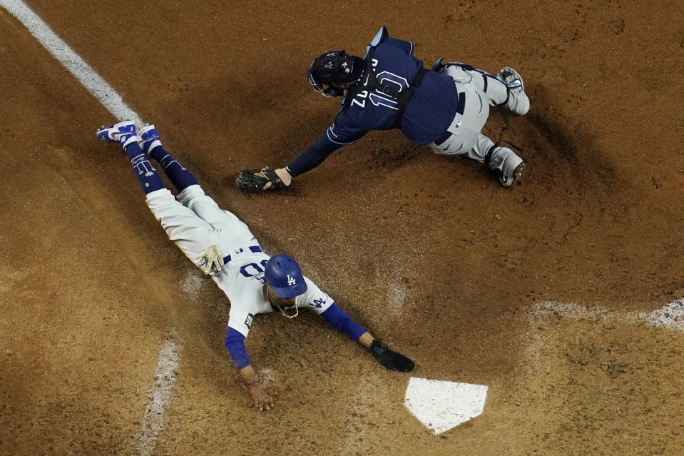 Los Angeles Dodgers' Mookie Betts scores past Tampa Bay Rays catcher Mike Zunino on a fielders choice by Max Muncy during the fifth inning in Game 1 of the baseball World Series Tuesday, Oct. 20, 2020, in Arlington, Texas. (AP Photo/David J. Phillip)