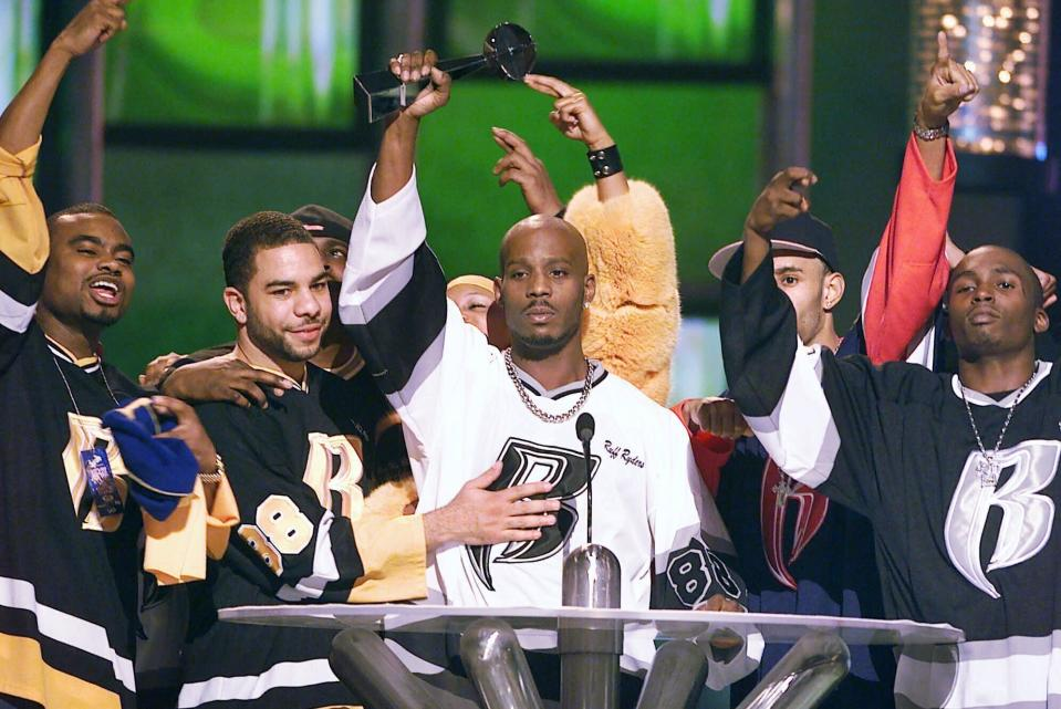 FILE - DMX, center, accepts the R&B Album Artist of the Year during the 1999 Billboard Music Awards in Las Vegas, on Dec. 8, 1999. The rapper will be mourned at a memorial with family and close friends at the Barclays Center in New York on Saturday. The event will be closed to the public due to pandemic conditions. (AP Photo/Laura Rauch, File)