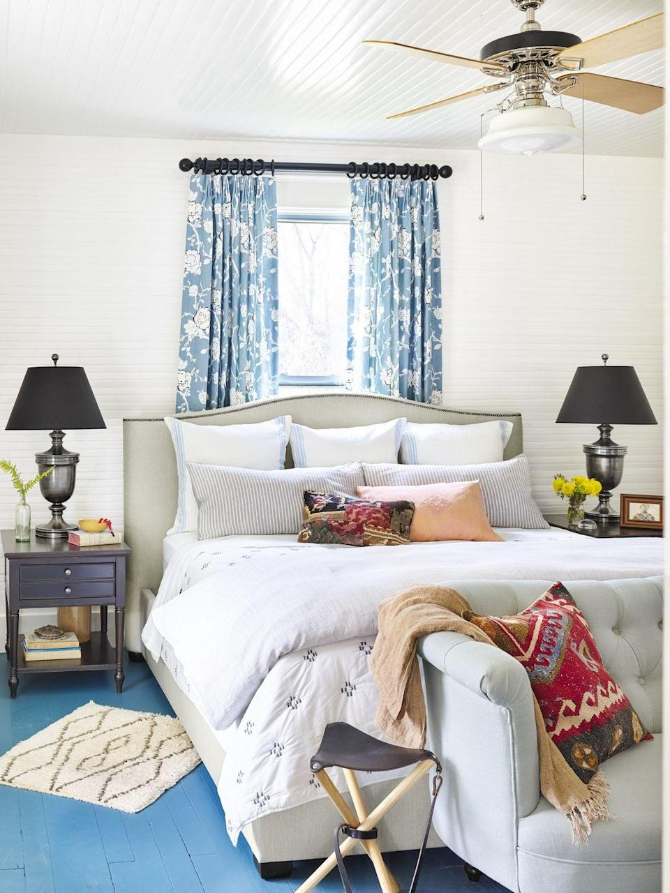 <p>If you've got a case of lackluster flooring, bring on the paint. Bright blue planks paired with white walls flip the usual decor combo in this bedroom. </p>