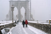 People make their way across the Brooklyn Bridge during the second snowstorm to buffet the area in less than a week, Sunday, Feb. 7, 2021, in New York. (AP Photo/Kathy Willens)