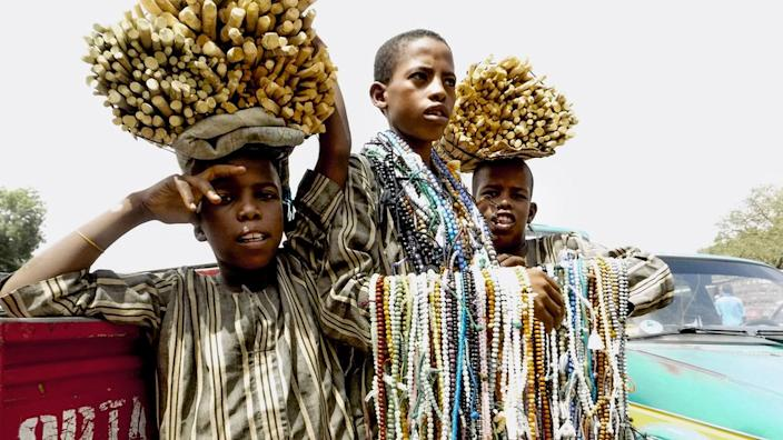 Three boys hawking wares in Nigeria