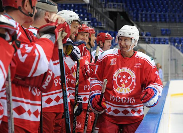 Russian President Vladimir Putin (R) smiles as he walks past NHL hockey star Alexander Ovechkin (3L) during the Hockey legends team match against the students of the Sirius Center for Gifted Children in Sochi on September 1, 2015. AFP PHOTO / RIA NOVOSTI / POOL / MICHAEL KLIMENTYEV (AFP Photo/Michael Klimentyev)