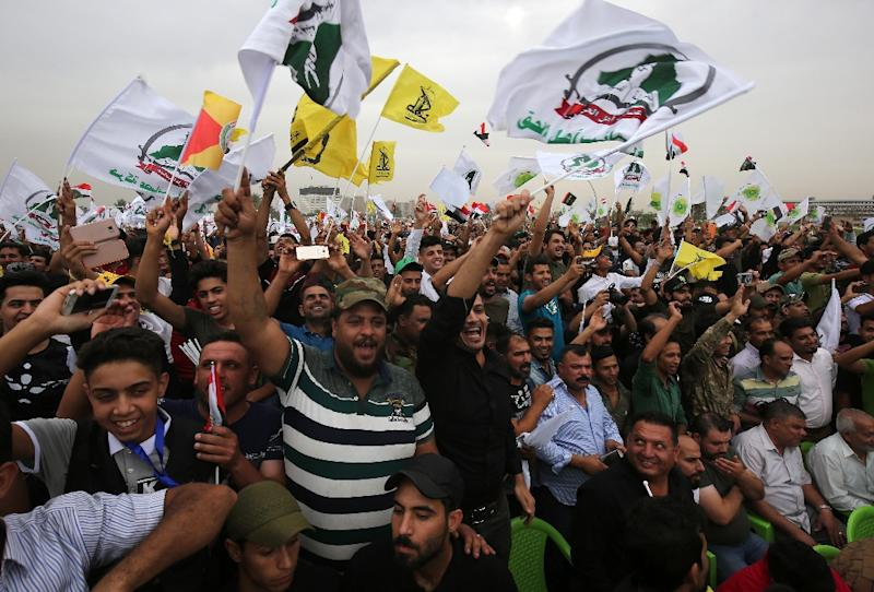 Supporters of Iraq's Hashed al-Shaabi paramilitary units wave flags during a campaign rally in Baghdad ahead of the May 12, 2018 parliamentary election (AFP Photo/AHMAD AL-RUBAYE)