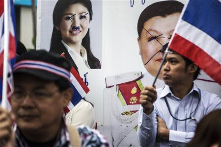 Anti-government protesters stand near the defaced pictures of Thai Prime Minister Yingluck Shinawatra (back L) and Thai Police Major General Wimon Pao-In as they take part in a rally in Bangkok's financial district January 23, 2014. REUTERS/Nir Elias