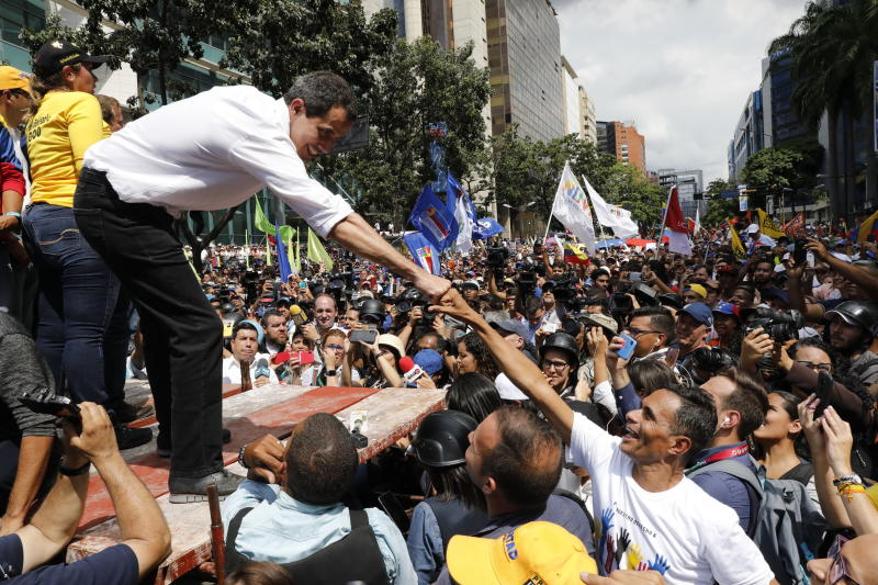 Opposition politician Juan Guaido fist bumps with a supporter during a rally, in Caracas, Venezuela, Saturday, Nov. 16, 2019.  Guaido called nationwide demonstrations to re-ignite a campaign against President Nicolas Maduro launched in January that has lost steam in recent months. (AP Photo/Ariana Cubillos)