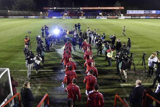 British Army and German Bundeswehr teams walk out onto the pitch for a soccer match at Aldershot Town FC stadium in Aldershot in south England, December 17, 2014. The two teams were playing each other in a 'Game of Truce' soccer match, commemorating 100 years since the famous peaceful interlude to fighting in World War I when members of the opposing British and German forces played a game of soccer in No Man's Land on Christmas Day 1914. REUTERS/Toby Melville (BRITAIN - Tags: SPORT SOCCER POLITICS ANNIVERSARY CONFLICT MILITARY)