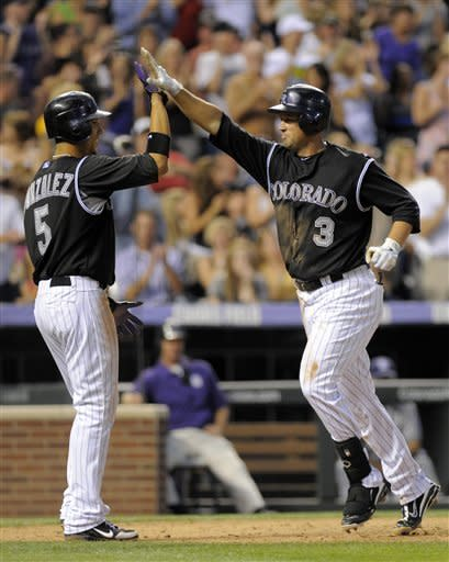 Colorado Rockies' Michael Cuddyer (3) high-fives teammate Carlos Gonzalez (5) after driving him in on a two-run home run hit off San Diego Padres relief pitcher Alex Hinshaw during the eighth inning of a baseball game in Denver, Friday, June 29, 2012. (AP Photo/Jack Dempsey