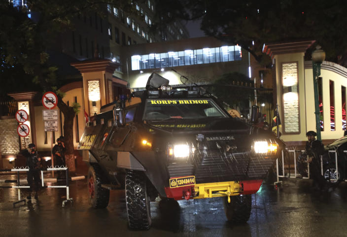 Police officers stand guard near an armored vehicle at the National Police Headquarters following a suspected militant attack in Jakarta, Indonesia, Wednesday, March 31, 2021. A woman entered the Indonesian National Police Headquarters in Jakarta and pointed a gun at several officers before being shot dead by police, in the latest in a series of militant attacks in the world's most populous Muslim nation. (AP Photo/Dita Alangkara)