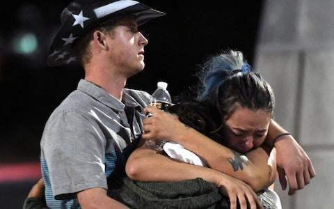 <span>People hug and cry after the mass shooting at the Route 91 Harvest country music festival</span> <span>Credit: Ethan Miller/Getty </span>