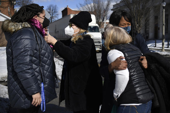 In this Saturday, Feb. 20, 2021, photo, Mia Schultz, president of the Rutland area branch of the NAACP, left, is helped with a scarf made for her by friend MaryJane Sarvis, second from left, while town Select Board candidate Tina Cook, right, embraces friend and supporter Laura Payne as they all meet outside Town Offices in Bennington, Vt. Cook came up short in the March 2 election in her effort to become the first African American elected to the board. (AP Photo/Jessica Hill)