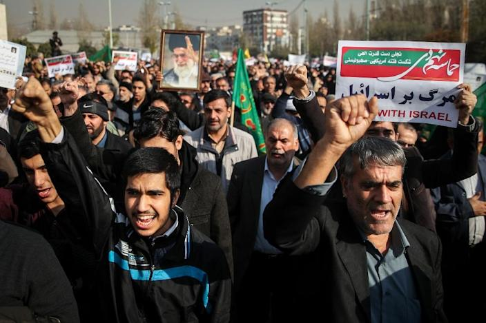 Iranians chant slogans in support of the regime as they march towards the Imam Khomeini grand mosque in Tehran on December 30, 2017 (AFP Photo/HAMED MALEKPOUR)