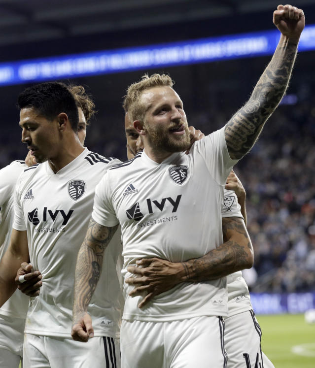 Sporting Kansas City forward Johnny Russell raises his fist in celebration of his first goal of the night during the first half of an MLS soccer match against the Vancouver Whitecaps in Kansas City, Kan., Friday, April 20, 2018. (AP Photo/Orlin Wagner)
