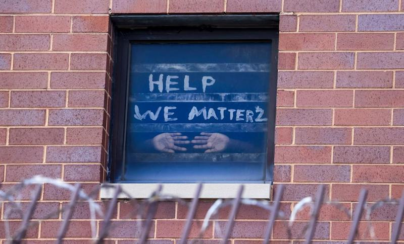 An inmate in the maximum security unit of the Cook County Jail in Chicago presses his hands against the window, below a plea for help.