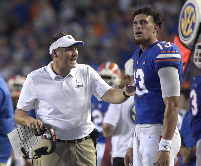 Florida head coach Dan Mullen, left, talks with quarterback Feleipe Franks (13) during a 2018 college football game. (AP)