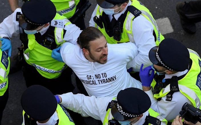 Police detain a demonstrator during an anti-lockdown protest in London - TOBY MELVILLE/REUTERS