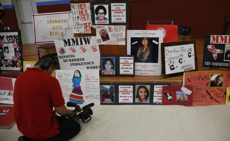 FILE - In this June 14, 2019, file photo, a photographer videos signs in memory of missing and murdered indigenous women following a march to call for justice for missing and murdered indigenous women at the Cheyenne and Arapaho Tribes of Oklahoma in Concho, Okla. A key congressional committee is holding a hearing on a slate of legislation aimed at addressing the deaths and disappearances of Native American women. The bills before the U.S. Senate Committee on Indian Affairs would require law enforcement to submit annual reports to Congress to give lawmakers a better handle on the number of cases. (AP Photo/Sue Ogrocki, File)