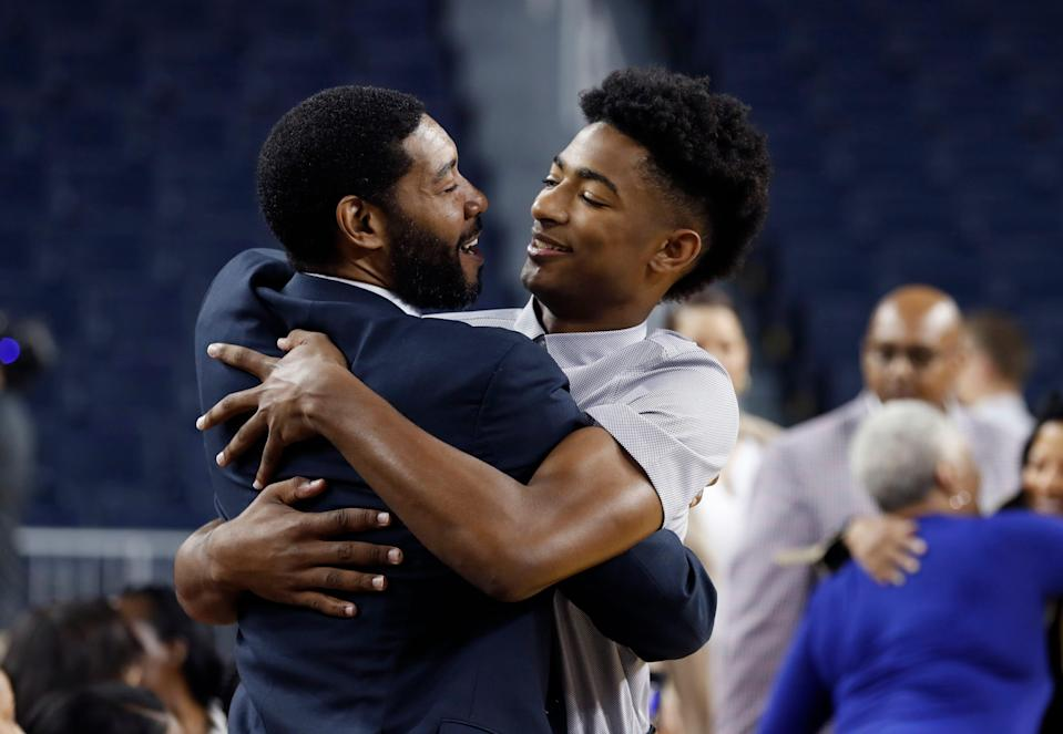 Retired NBA and former Michigan player Jimmy King, left, embraces Jace Howard before Jace's father Juwan is introduced as Michigan's new men's basketball coach on May 30, 2019.