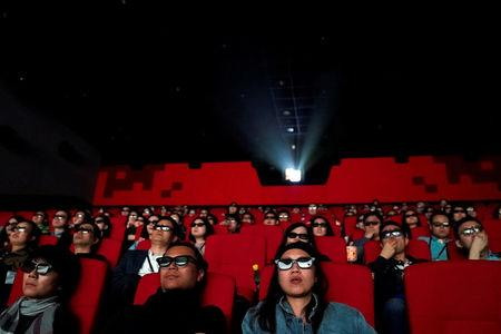FILE PHOTO: People watch a movie at a cinema in Wanda Group's Oriental Movie Metropolis ahead of its opening, in Qingdao