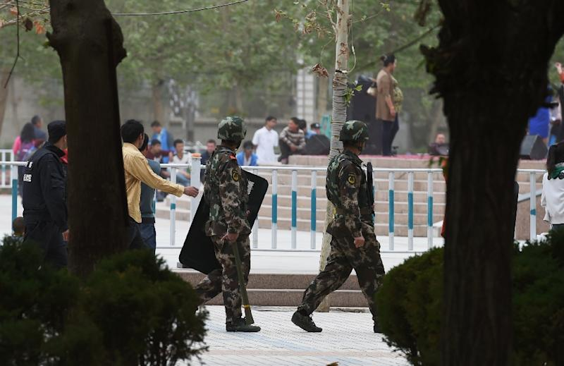 Paramilitary police patrol beside the central square in Hotan, in China's western Xinjiang region (AFP Photo/Greg Baker)