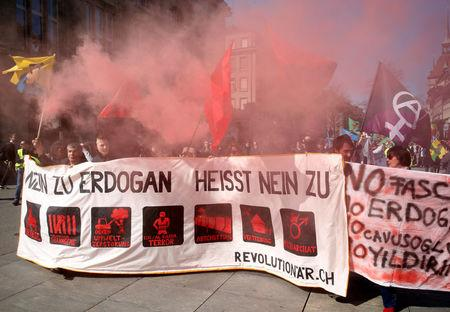"People hold banners and flags during a demonstration against Erdogan dictatorship and in favour of democracy in Turkey in Bern, Switzerland March 25, 2017. The bannerr reads ""Say no to Erdogan"" REUTERS/Ruben Sprich"
