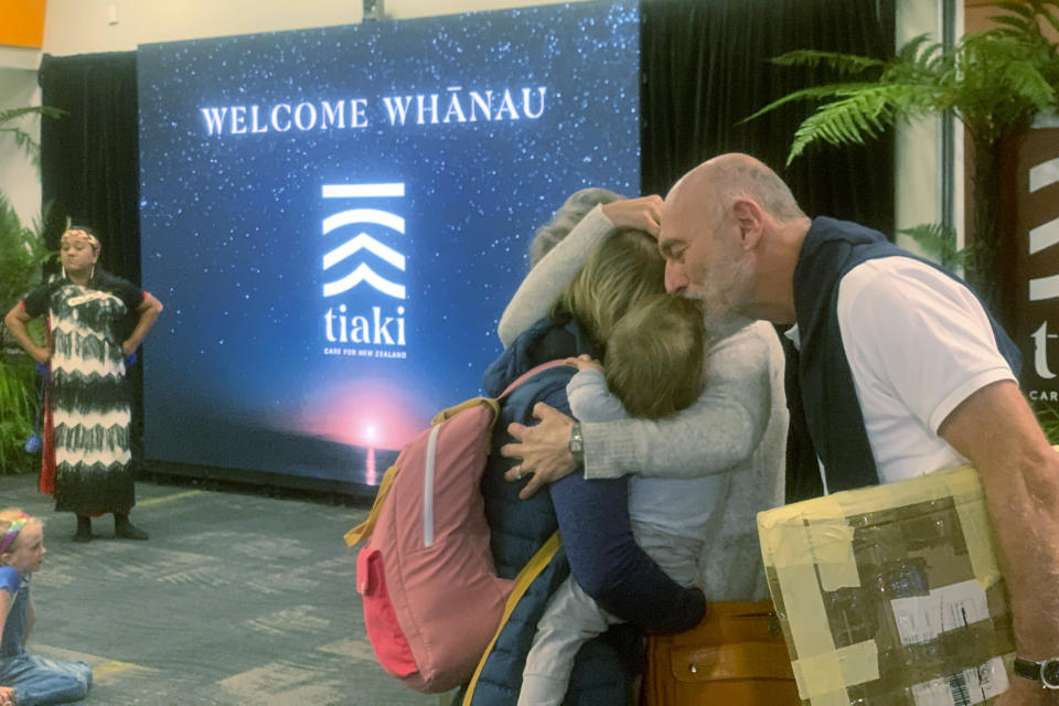 Passengers arriving from Sydney at the Wellington International Airport hug loved ones in Wellington, New Zealand Monday, April 19, 2021. The start of quarantine-free travel was a relief for families who have been separated by the coronavirus pandemic as well as to struggling tourist operators. (AP Photo/Nick Perry)