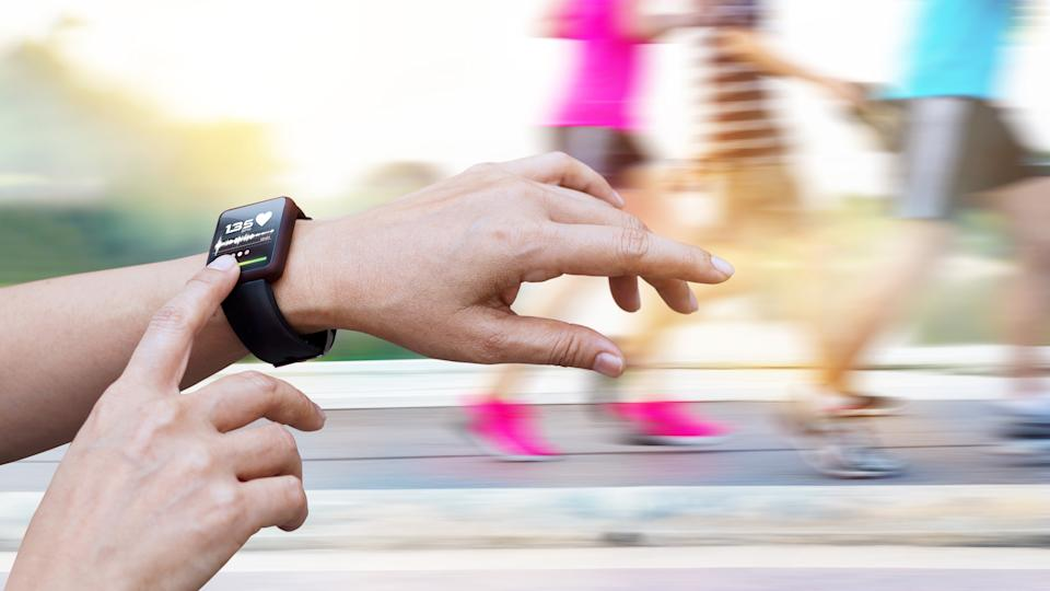 Woman checking up heart rate from smart watch on people running background