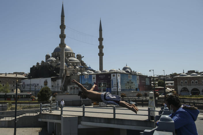 Backdropped by the historical Yeni Cami (New Mosque), a youth jumps from the Galata Bridge into the Golden Horn leading to the Bosphorus Strait separating Europe and Asia, in Istanbul, Friday, May 14, 2021.Turkey is in the final days of a full coronavirus lockdown and the government has ordered people to stay home and businesses to close amid a huge surge in new daily infections. But millions of workers are exempt and so are foreign tourists. Turkey is courting international tourists during an economic downturn and needs the foreign currencies that tourism brings to help the economy as the Turkish lira continues to sink. (AP Photo/Emrah Gurel)