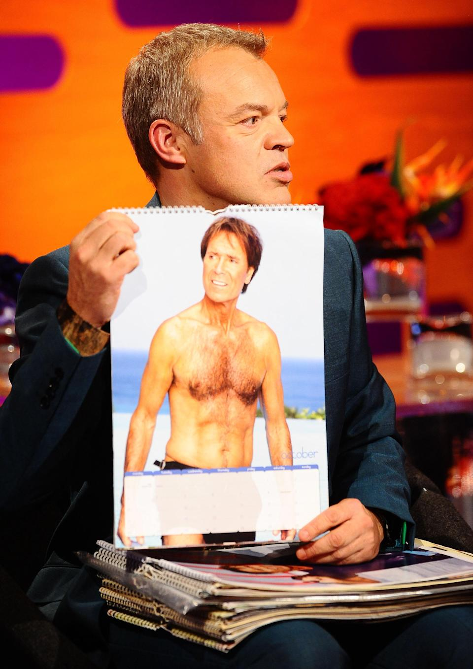 Presenter Graham Norton holds up a calendar featuring guest Sir Cliff Richard during the filming of the Graham Norton Show at The London Studios, south London, to be aired on BBC One on Friday evening.   (Photo by Ian West/PA Images via Getty Images)